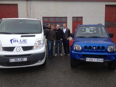 Blue Car Rental staff with airport shuttle and Jimny.